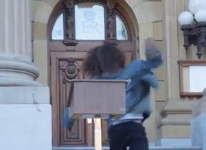 Bernard the Roughneck throwing his shoe at the Alberta Legislature. Photo: Video screen capture.